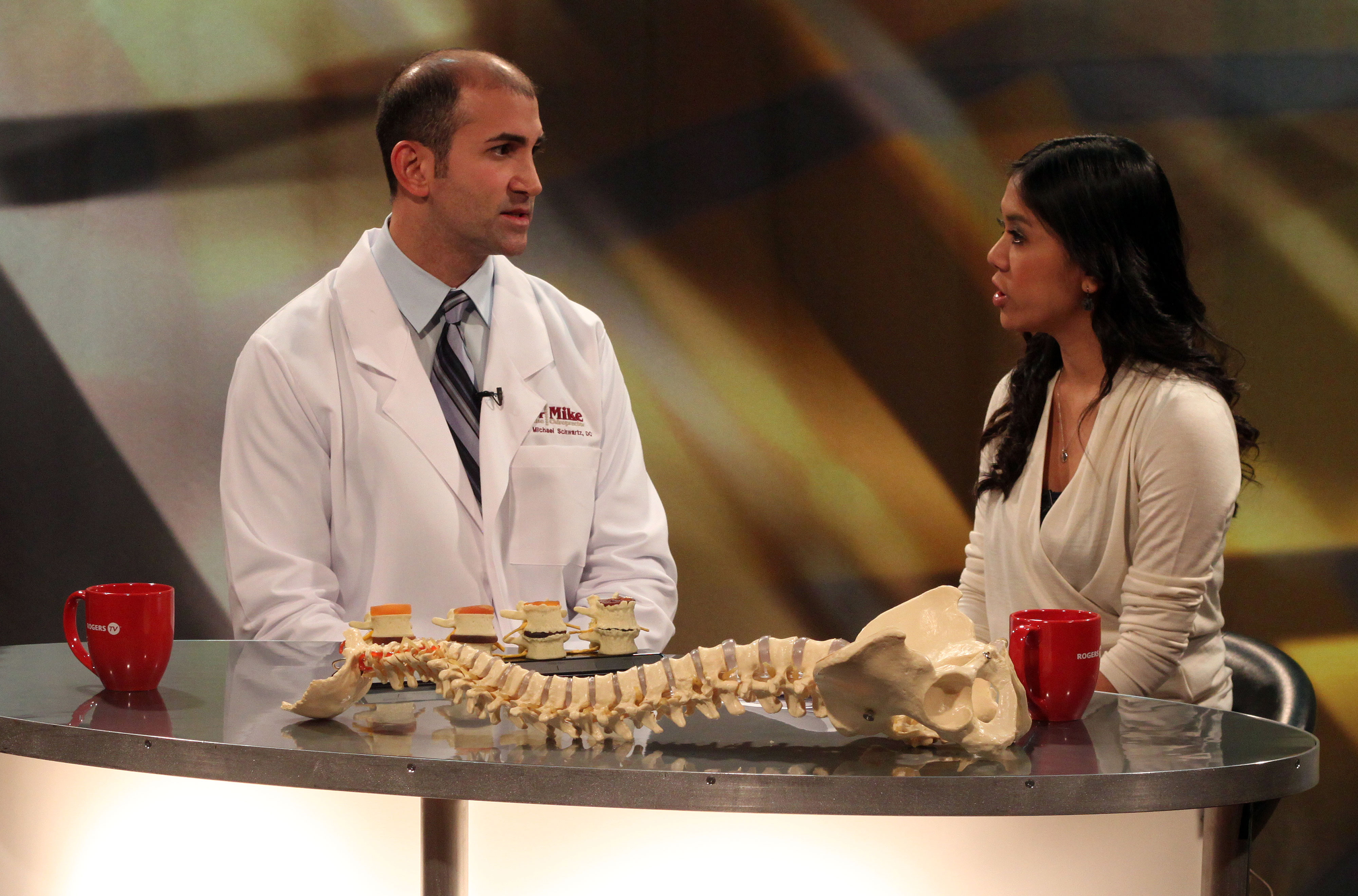 "Dr. Mike the Chiropractor, a.k.a. Dr. Michael A. Schwartz, DC, explains how the human spine works and how to take better care of it, to Emily Anonuevo, host of Rogers' ""In the Know."""